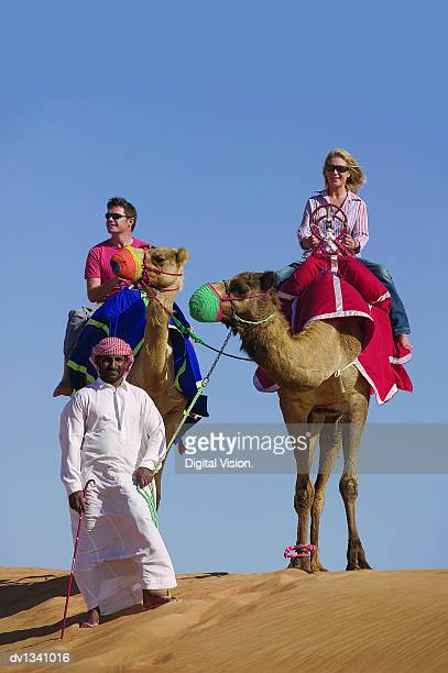 Two tourists Riding Camels in the Desert Following a Man in Traditional Middle Eastern Clothing