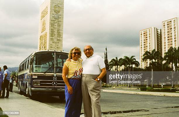 Two tourists stand and pose for a photo with a Mercedes Benz tour bus in the background in front of the Monumento de La Nacion A Sus Proceres in...