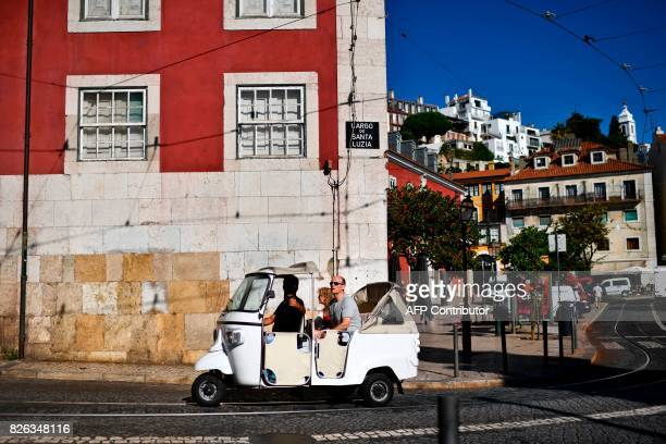 Two tourists take a ride in a tuk tuk in Alfama neighborhood Lisbon on August 2 2017 / AFP PHOTO / PATRICIA DE MELO MOREIRA