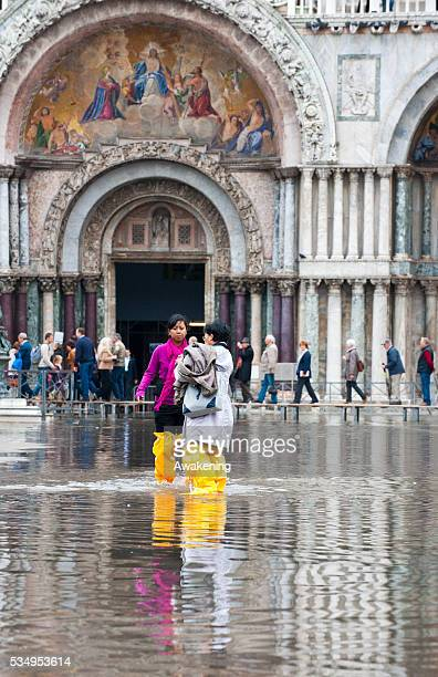 Two tourists take pictures during today first high tide of the season in Venice with water reaching the level at sea of 110 centimetres above sea...