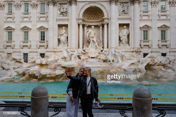 Two tourists take selfies in front of the Fontana di Trevi in Rome on 12 October 2020 The data of the Covid19 positives in Rome grow to 158 in the 24...