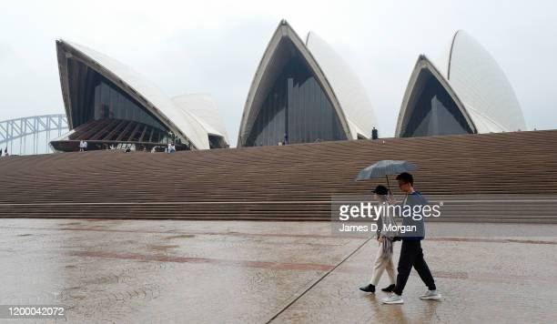 Two tourists to Australia hold their umbrella as they walk past the Opera House on January 17 2020 in Sydney Australia A severe thunderstorm warning...