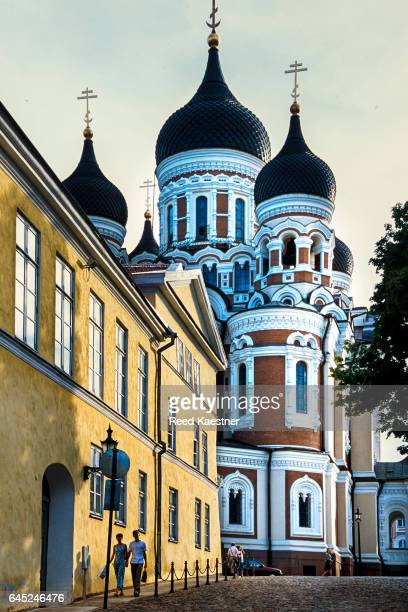 Two tourists walk down a sun filled street in Tallinn, Estonia with the Alexander Nevsky Cathedral in the background.