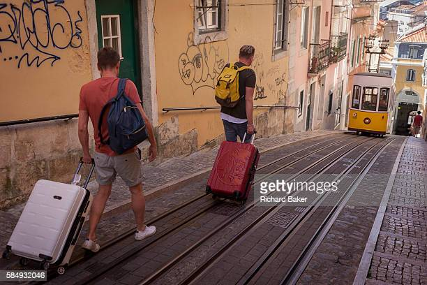 Two tourists walk downhill with their baggage towards one of the two cars of the funicular railway climbing the steep gradient of on Rua de Bica de...