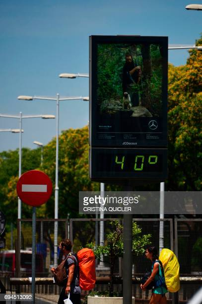 Two tourists walk under a billboard that shows the temperature at 40 degrees celsius in Sevilla on June 10 2017 QUICLER