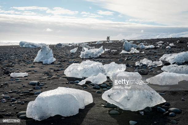 two tourists walking at horizon, ice floes on black beach, diamond beach, fjallsarlon glacier lagoon, east iceland, iceland - austurland stock-fotos und bilder