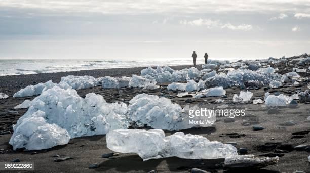 two tourists walking on the beach, ice floes on black lava sand, diamond beach, fjallsarlon glacier lagoon, east iceland, iceland - austurland stock-fotos und bilder