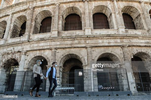 Two tourists with face masks hold hands near the Colosseum during the Coronavirus emergency, on March 11 in Rome, Italy. The Italian government has...