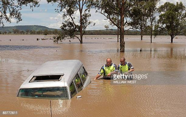 Two tow truck operator swades into the flood waters to tow a fourwheel drive to dry ground some 80 kilometres west of Brisbane on November 21 as...