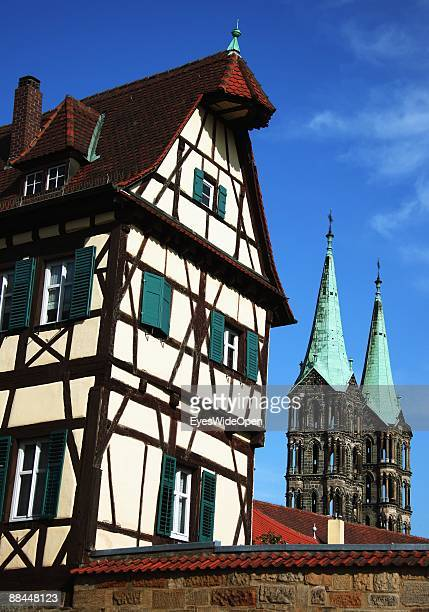 Two towers of the dome of Sankt Peter and St Georg and a traditional house on June 11 2009 in Bamberg Germany Bamberg is listed as a World Heritage...