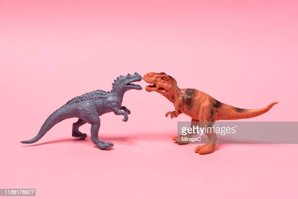 two toy dinosaurs face to face - funny animals stock pictures, royalty-free photos & images