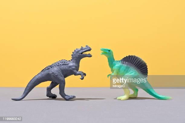 two toy dinosaurs face to face - konfrontation stock-fotos und bilder