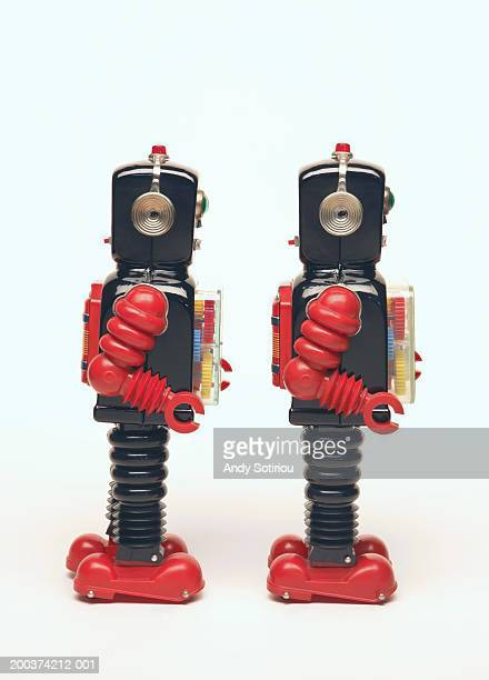 Two toy robots side by side, side view