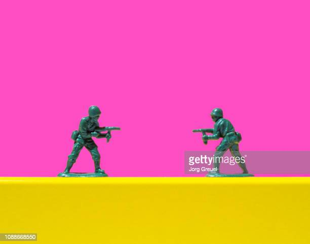 two toy soldiers pointing guns at each other - rivaliteit stockfoto's en -beelden