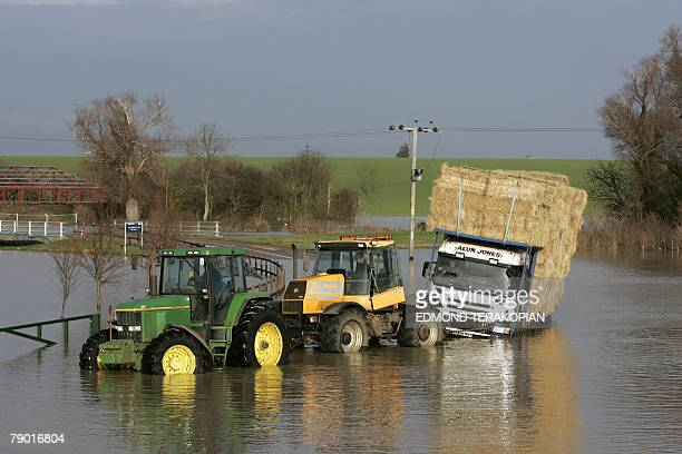 Two tractors tow a truck near the Huntingdon Race Course and car park submerged by flood waters 16 January 2008 in the village of Brampton following...