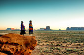 Two Traditional Navajo Native American Sisters In Monument Valley Tribal Park on a Rocky Butte Enjoying a Sunrise or Sunset