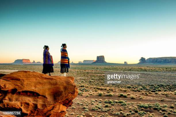 two traditional navajo native american sisters in monument valley tribal park on a rocky butte enjoying a sunrise or sunset - indigenous culture stock pictures, royalty-free photos & images