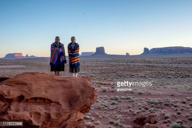 two traditional navajo native american sisters in monument valley tribal park on a rocky butte enjoying a sunrise or sunset - apache indian stock pictures, royalty-free photos & images
