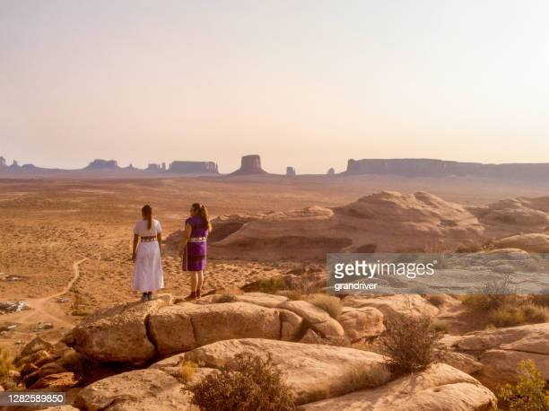 two traditional navajo native american sisters in monument valley tribal park on a rocky butte enjoying a sunrise or sunset - cherokee culture stock pictures, royalty-free photos & images