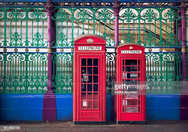 Two traditional red telephone boxes,against ironwork railings,Smithfield Market, London