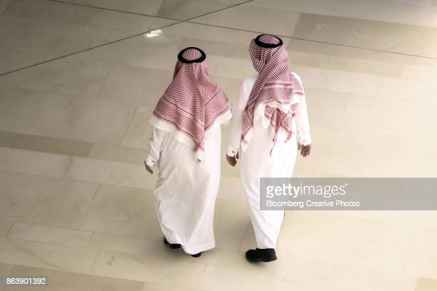 Two traditionally dressed men walk together in Saudi Arabia