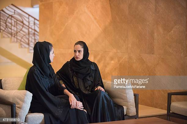 Two Traditionally Dressed, Middle Eastern Young Women Having Serious Discussion