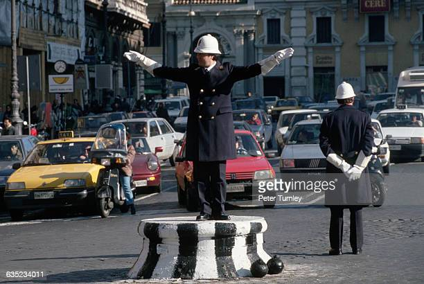 Two traffic officers direct traffic around Piazza Venetia.