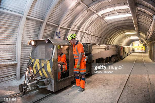 Two train operators in transport tunnel of deep coalmine