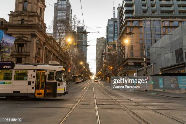 Two trams operating on a quiet intersection in the Melbourne Central business district on August 06 2020 in Melbourne Australia Retail stores across...