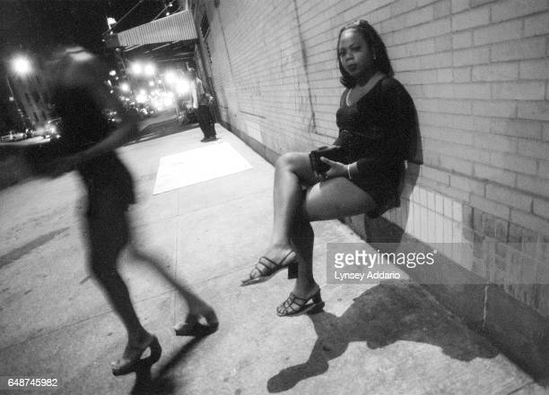 Two transgendered prostitutes stop to relax momentarily while strolling through the meatpacking district in New York City in June 1999