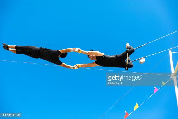 two trapeze artists flying together in the sky - trust stock pictures, royalty-free photos & images