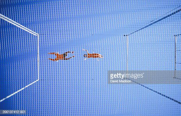 Two trapeze artists performing release move, view through safety net