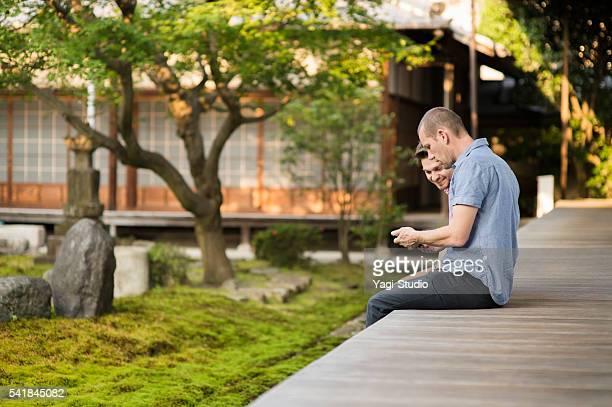 two travelers watching smartphone in a japanese temple - shrine stock pictures, royalty-free photos & images