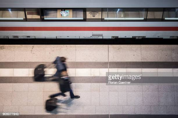 Two traveller with trolley bags walks along a train on January 11 2018 in Berlin Germany