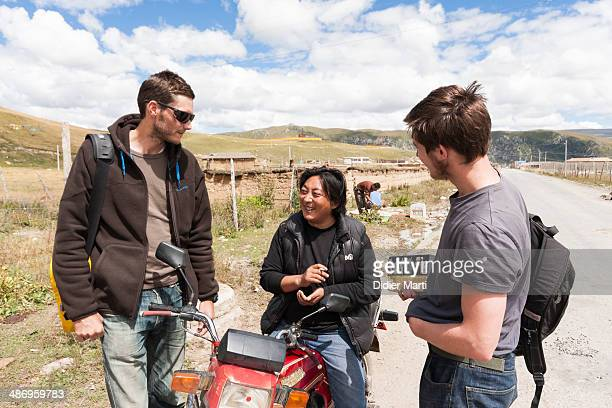 Two travellers asking questions to a local man in the countryside of Sichuan province in China