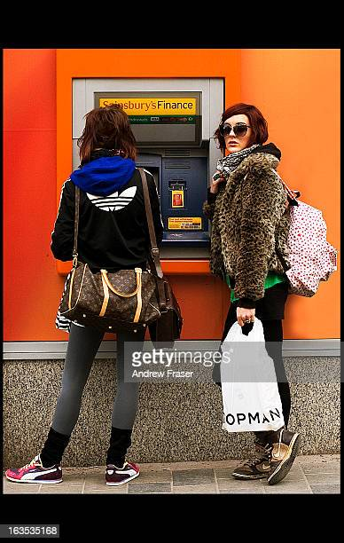 Two trendy girls with bags at cashpoint/auto-teller, Sauchiehall Street, Glasgow, Scotland, 2011