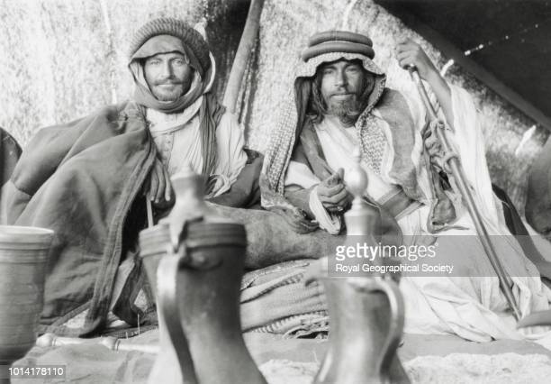 Two tribesmen in a tent at the encampment of Shaikh Auda Abu Tayyi of the Huwaitat Encampment at Tor alTubaiq [Jabal Tubaiq] The men's names are...