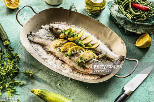 Two trout stuffed with herbs and lemon slices in fish pan
