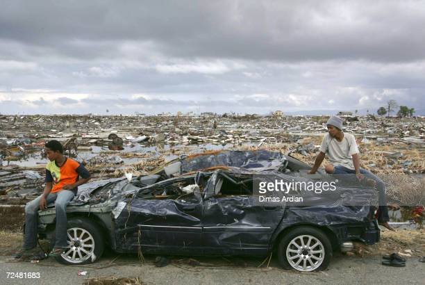 Two tsunami survivors sit on top of a car which was damaged by the tsunami January 9 2005 in Banda Aceh Indonesia An estimated 150000 were killed in...