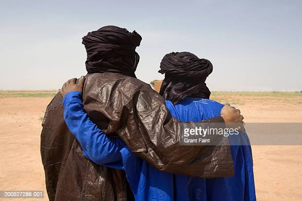 two tuareg men embracing side by side, looking at desert, rear view - tuaregue imagens e fotografias de stock