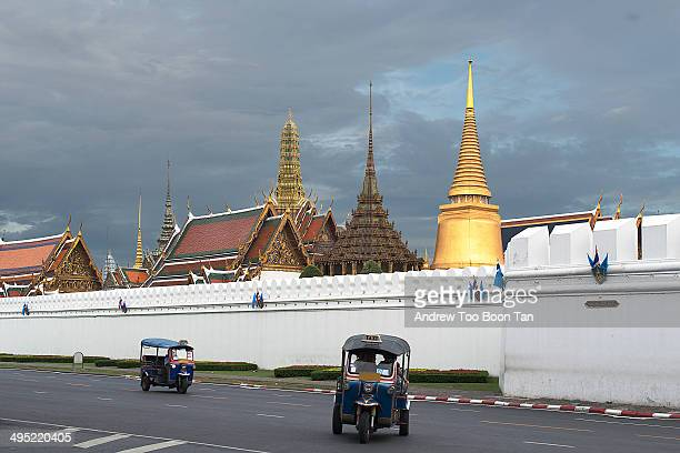 Two tuk-tuks drive past the Grand Palace in Bangkok as the skies darken with an approaching thunderstorm.