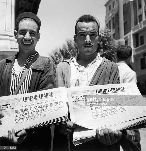 Two Tunisian newspaper sellers presenting the front page of the newspaper TUNISIE-FRANCE on August 9, 1954 in Tunis. The newspaper reports the...