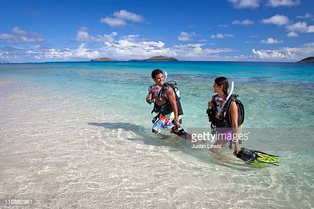 two two divers walking out of water in tropics