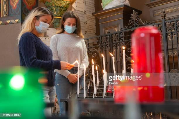 twee twee vrouwen die kaarsen binnen de kerk in tijden van coronavirus aansteken - gelovige stockfoto's en -beelden