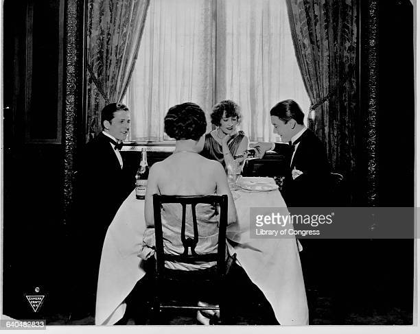 Two typical young couples of the 1920s enjoy mineral water with their dinner for an advertisment of the water