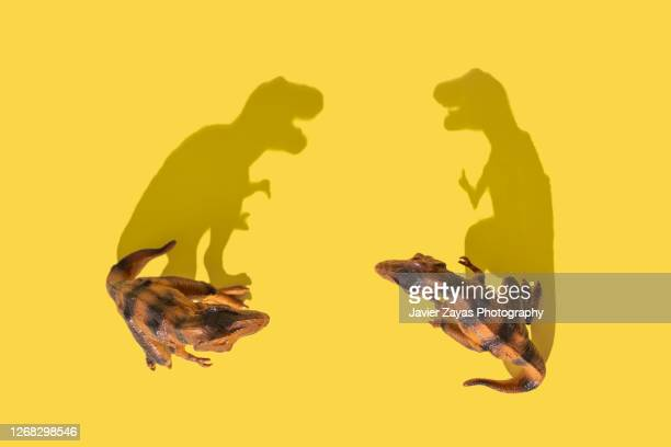 two tyrannosaurus rex fighting on yellow background - two animals stock pictures, royalty-free photos & images