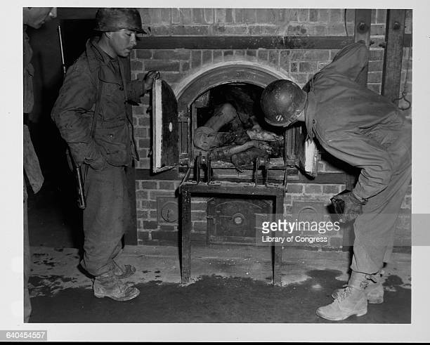 Two U S soldiers look at a corpse in an oven at a liberated concentration camp in Germany April 824 1945