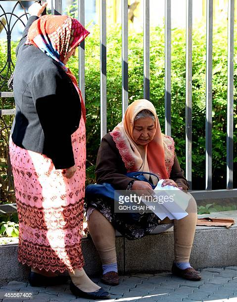 Two Uighur women wait after they were disallowed entry to the Urumqi Intermediate People's court as the trial of Ilham Tohti a former economics...