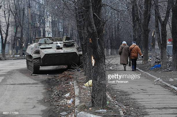 Two Ukrainian women walk past a wrecked armored personnel carrier as Debaltseve copes with the aftermath of a siege and then capture by Russianbacked...