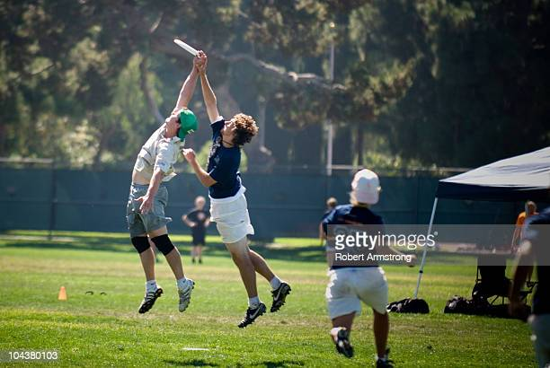 Two ultimate Frisbee players simultaneously leap to catch a disc during a game at the Southern California Ultimate Frisbee Sectionals tournament.